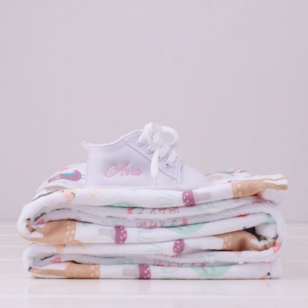 Folded forest minky blanket with white personalised baby shoes on top
