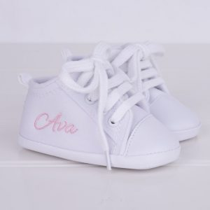 White baby shoes personalised in pink with the name Ava