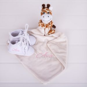 Giraffe baby comforter & white baby shoes both personalised with the name Elio