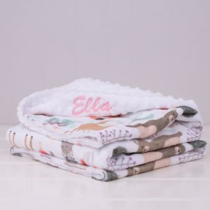 White forest minky blanket with printed animals, folded and embroidered with name Ella in pink