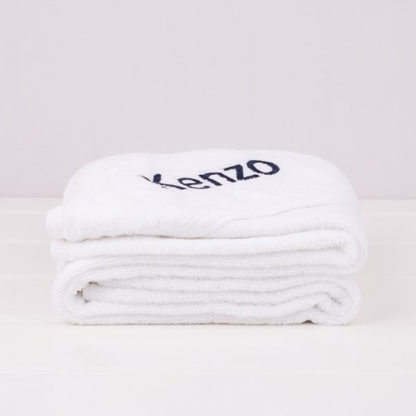White baby's hooded towel folded and personalised with the baby name Kenzo in navy blue