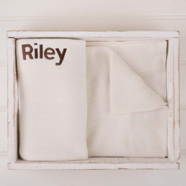 White knitted personalised baby blanket embroidered with the name Riley