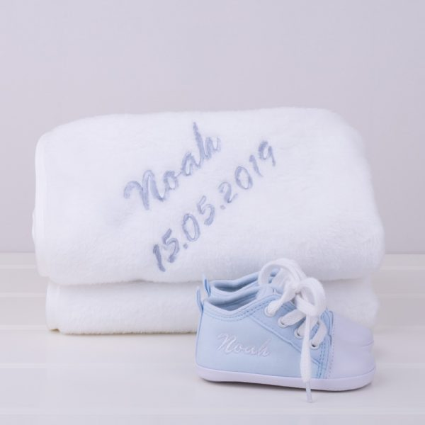 Blue baby shoes & white fleece blanket both personalised with the name Noah