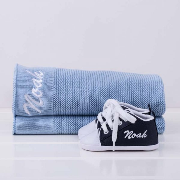 Navy Blue Baby Shoes in front of a blue kitted blanket both personalised with the name Noah in white