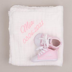 White muslin baby's blanket & pink personalised baby shoes both embroidered with the name Mia with grey background