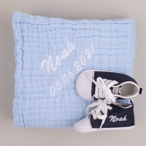 Blue muslin baby's wrap & navy personalised baby shoes both embroidered with the name Noah with grey background
