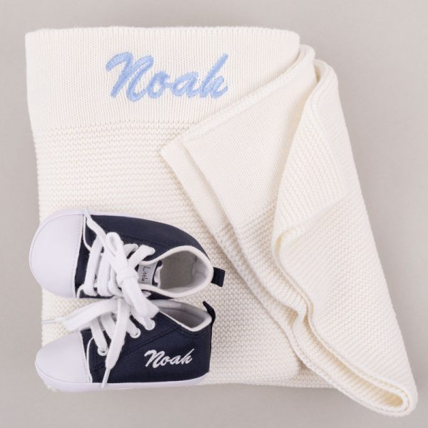 Navy Blue Shoes in front of a white kitted blanket both personalised with the name Noah