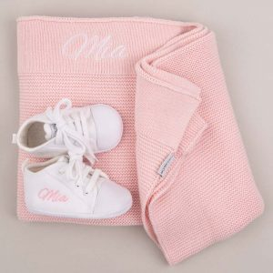 White Baby Shoes in front of a Pink Knitted Blanket and both embroidered with the name Mia