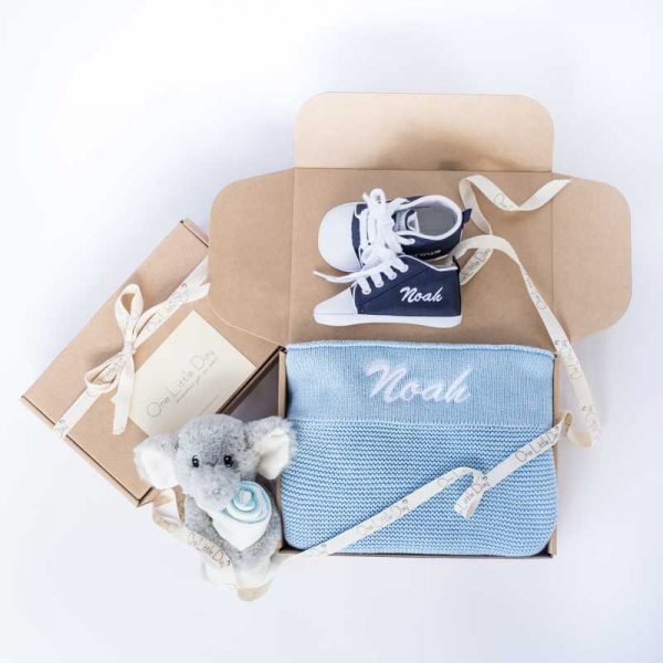 One Little Day gift boxes with blue knitted blanket, navy blue baby shoes and elephant comforter