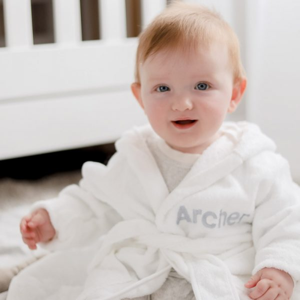 Baby wearing white personalised baby's robe embroidered with the name Archer