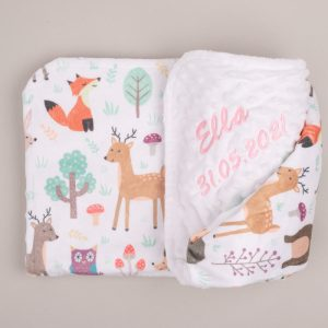 White forest minky blanket with printed animals, folded and embroidered with name Ella in pink grey background