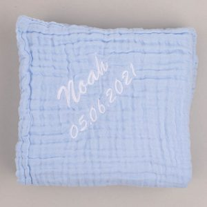 Large blue muslin baby's blanket in a box with the name Noah embroidered grey background