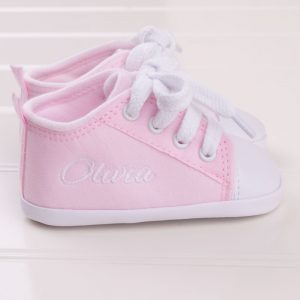 Pink baby shoes personalised with the name Olivia in white writing