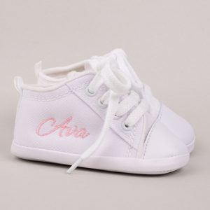 Personalised white baby shoes embroidered with the name Ava with grey background