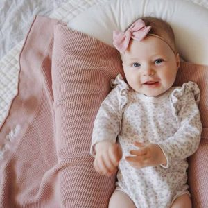 Baby laying on blush pink knitted cotton baby's blanket