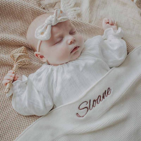 Baby laying under a white knitted cotton blanket that is personalised with the name Sloane