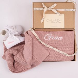 One Little Day gift boxes with blush pink knitted blanket, and white baby shoes