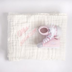 White muslin baby's blanket & pink personalised baby shoes both embroidered with the name Mia