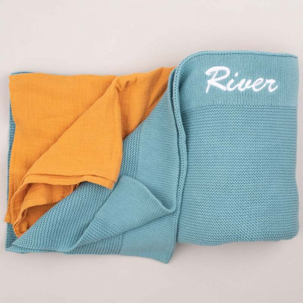 An Ocean Blue Knitted blanket personalised with the name River next to a yellow mustard wrap