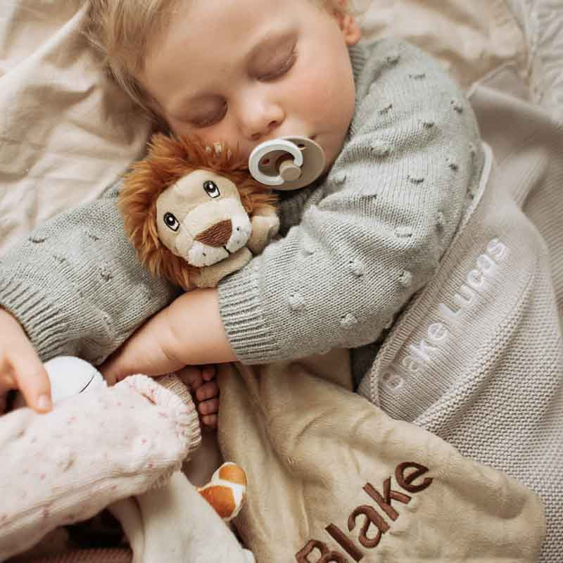 A baby cuddling lion comforter personalised with the name Blake