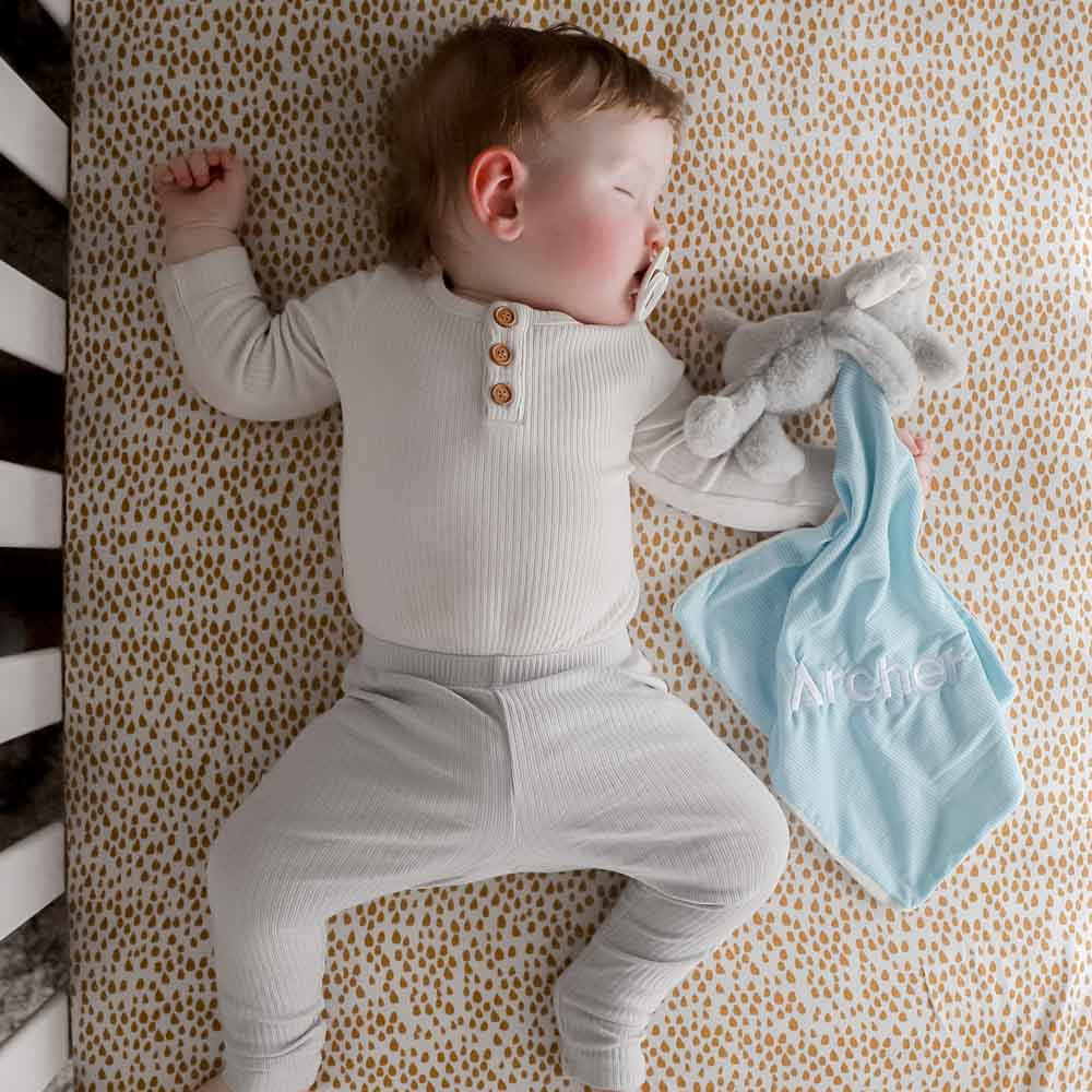 A baby sleeping with an elephant baby comforter which is embroidered with his name