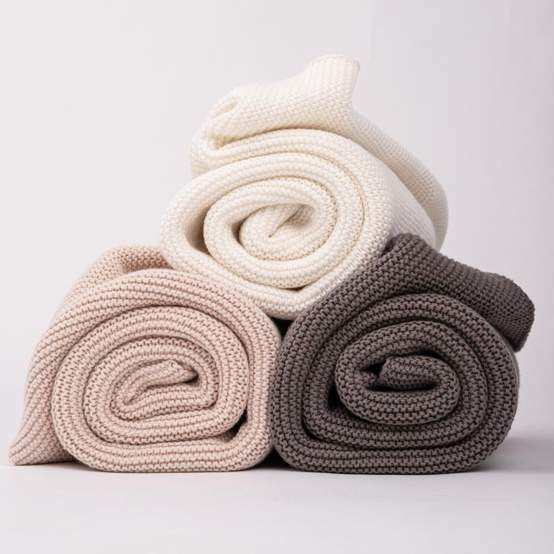 Three rolled up personalised knitted baby blankets