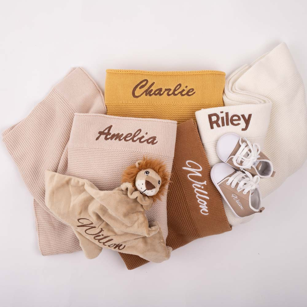 Four folded knitted blanket with a lion comforter & a pair of baby shoes. All items are personalised with baby names.