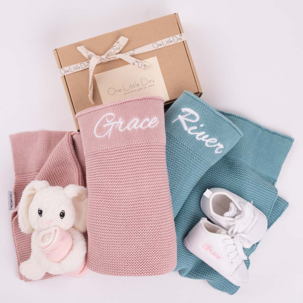 Two personalised knitted baby's blankets, a bunny comforter and a pair or personalised baby shoes